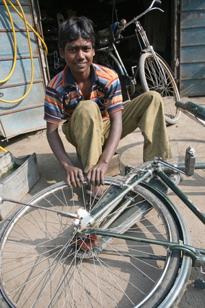 BARUIPUR, INDIA - JANUARY 13: Mechanic in the workshop repair the tire on a bicycle. The bicycle is in India, one of the main means of transport., Baruipur, West Bengal on January 13, 2009. Stock Photo - 10770208