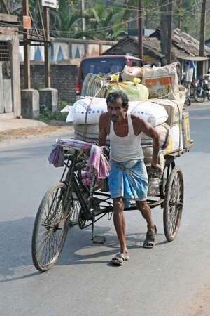 simplest: BARUIPUR, INDIA - JANUARY 13: Man pushing heavily loaded cycle rickshaw through the streets of, Baruipur. The cheaper and simplest public transportation which give poor people work, Baruipur, West Bengal, India on January 13, 2009