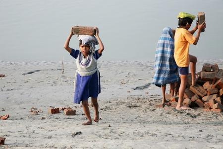 esclavo: SONAKHALI, INDIA - 17 de enero los ni�os trabajadores que transportan ladrillos en la cabeza en Sonakhali, Bengala Occidental, India el 17 de enero de 2009.