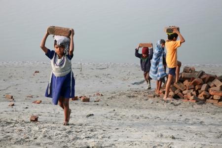 esclavo: SONAKHALI, INDIA - el 17 de enero ni�os trabajadores llevan ladrillos llevando sobre su cabeza en Sonakhali, West Bengal, India el 17 de enero de 2009. Editorial