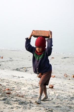 slave girl: SONAKHALI, INDIA - JANUARY 17 child workers carry bricks carrying it on his head in Sonakhali, West Bengal, India on January 17, 2009.