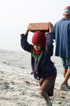 slave labor: SONAKHALI, INDIA - JANUARY 17 child workers carry bricks carrying it on his head in Sonakhali, West Bengal, India on January 17, 2009.