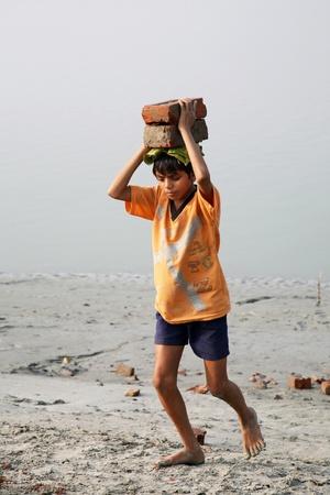 gente pobre: SONAKHALI, INDIA - 17 de enero los niños trabajadores que transportan ladrillos en la cabeza en Sonakhali, Bengala Occidental, India el 17 de enero de 2009.