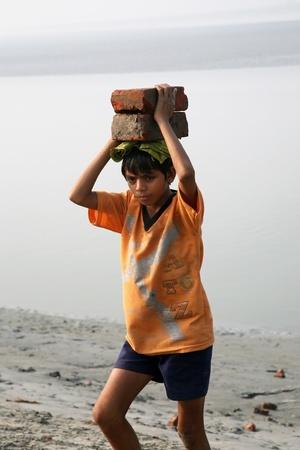 SONAKHALI, 인도 - 년 1 월 17 번째 노동자 월 17, 2009에 Sonakhali, 웨스트 벵골, 인도에 그의 머리에 그것을 들고 벽돌을 수행한다. 에디토리얼