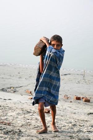 esclavo: SONAKHALI, INDIA - 17 de enero los niños trabajadores que transportan ladrillos en la cabeza en Sonakhali, Bengala Occidental, India el 17 de enero de 2009.