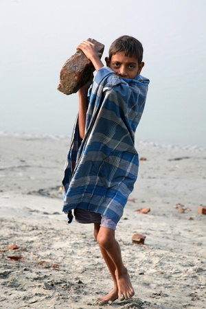 underpaid: SONAKHALI, INDIA - JANUARY 17 child workers carry bricks carrying it on his head in Sonakhali, West Bengal, India on January 17, 2009.