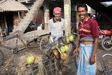 KUMROKHALI, INDIA - JANUARY 12: Selling a coconut on  market in Kumrokhali, West Bengal, India on January 12, 2009. 42% of India falls below the international poverty line of $1.25 a day