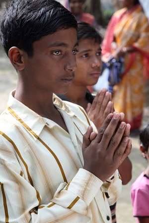 A group of young Bengali Catholics pray before a statue of the Blessed Virgin Mary, West Bengal, India