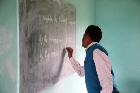 KUMROKHALI, INDIA - JANUARY 16: Teacher writes on blackboard at school on January 16, 2009, Kumrokhali, West Bengal, India Stock Photo - 10977284