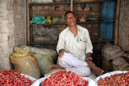 KUMROKHALI, INDIA - JANUARY 19: Man selling peppers on January 19, 2009, Kumrokhali, West Bengal, India. Food hawkers in India are generally unaware of standards of hygiene and cleanliness.