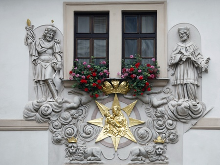 Prague, House of the Golden Well, Madonna and Child surrounded by saints on the facade of the house in Prague photo