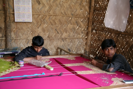 KUMROKHALI, INDIA - JAN 16: Indrajit, 17 and Anandalok, 15, Naskar working on the decoration of textiles in Kumrokhali, India on Jan 16, 2009.