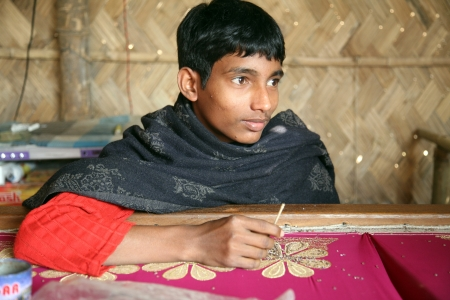 underpaid: KUMROKHALI, INDIA - JAN 16: Anandalok Naskar, 15,  working on the decoration of textiles in Kumrokhali, India on Jan 16, 2009.According to the statistics there are 20 million child laborers in the country Editorial