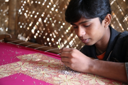 underpaid: KUMROKHALI, INDIA - JAN 16: Indrajit Naskar, 17,  working on the decoration of textiles in Kumrokhali, India on Jan 16, 2009.According to the statistics there are 20 million child laborers in the country