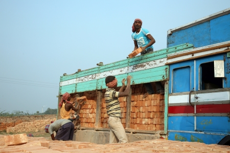 third world economy: SARBERIA,INDIA, JANUARY 16: Brick field workers carrying complete finish brick from the kiln, and loaded it onto a truck on January 16, 2009 in Sarberia, West Bengal, India.