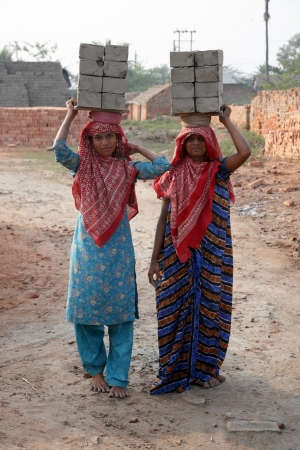 third world economy: SARBERIA,INDIA, JANUARY 16: Brick field workers carrying complete finish brick from the kiln on January 16, 2009 in Sarberia, West Bengal, India. Editorial