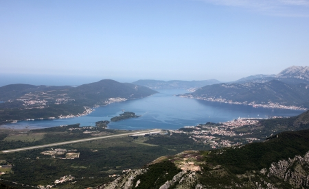 Panorama Site bay of Kotor with high mountains plunge into adriatic sea and town of Tivat, Montenegro photo
