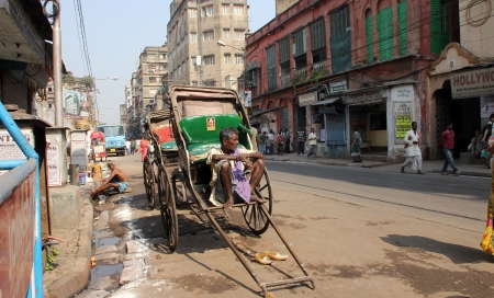 Rickshaw man waits for the customers on the streets on November 28, 2012 in Kolkata, India  Kolkata is the only city in India still having these hardworking human rickshaw workers