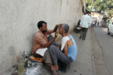 KOLKATA, INDIA - NOVEMBER 26  Street barber shaving a man using an open razor blade on a street in Kolkata, West Bengal, India on Nov 26, 2012
