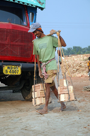 third world economy: Brick field workers carrying complete finish brick from the kiln, and loaded it onto a truck on January 16, 2009 in Sarberia, West Bengal, India