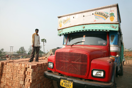 brick kiln: Brick field workers carrying complete finish brick from the kiln, and loaded it onto a truck on January 16, 2009 in Sarberia, West Bengal, India