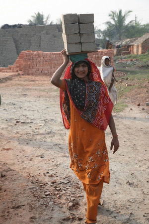 third world economy: Brick field workers carrying complete finish brick from the kiln on January 16, 2009 in Sarberia, West Bengal, India
