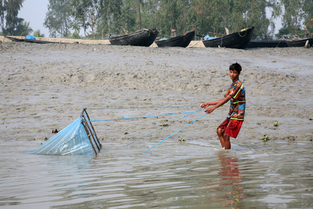 india fisherman: Fisherman uses fishing net in a traditional way for fishing in a Ganges river  on January 19, 2009 in Gosaba, West Bengal, India