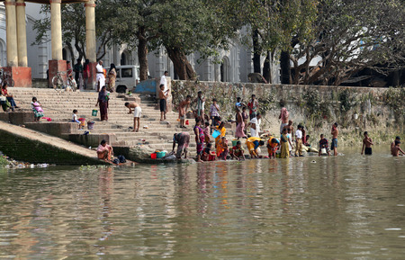 dome of hindu temple: Hindu people bathing in the ghat near the Dakshineswar Kali Temple in Kolkata on February 14, 2014  At present time this river is being polluted tremendously