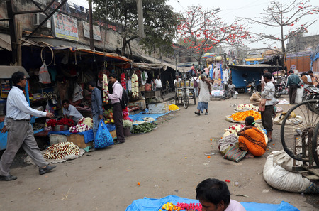 People buying and selling flowers and garlands at the flower market next to a railway track on February 15, 2014 in Kolkata  Calcutta , West Bengal, India