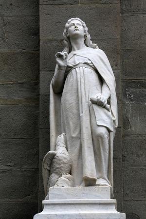 Saint John the Evangelist statue on the portal of the Saint John the Baptist church in Riomaggiore, Liguria, Italy
