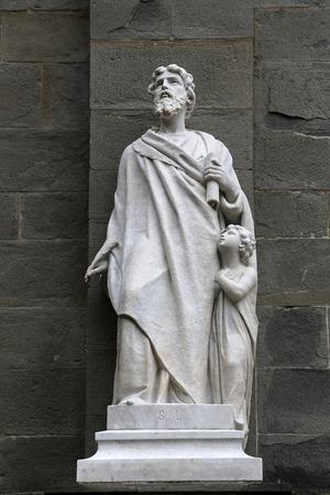 Saint Matthew the Evangelist statue on the portal of the Saint John the Baptist church in Riomaggiore, Liguria, Italy Фото со стока