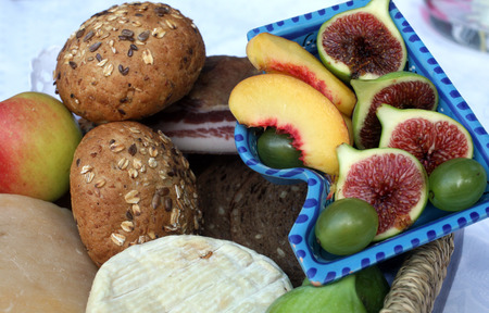 Rustic still life of bread, cheese, bacon and figs in a wicker basket photo