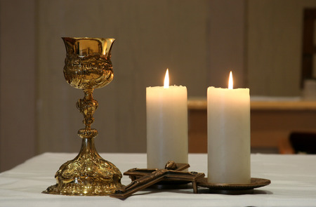 Golden chalice and two burning candles photo