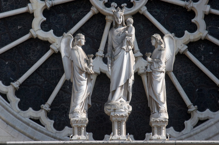 beheaded: Sculpture of the Virgin and Child flanked by angels, Rose window, Facade of Notre Dame de Paris Stock Photo