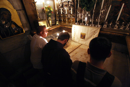 Pilgrims pray at the tomb of Jesus in the Church of the Holy Sepulchre, traditional site of the crucifixion, burial, and resurrection of Jesus, on October 01, 2006
