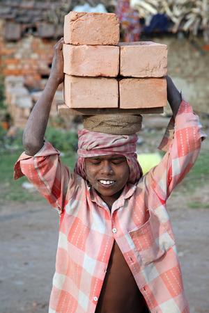 Steenbakkerij werknemers die volledige afwerking baksteen van de oven op 16 januari 2009 in Sarberia, West-Bengalen, India.