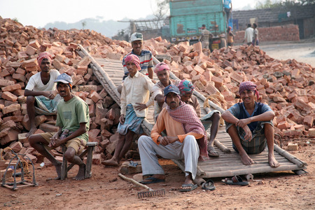 brick kiln: Brick field workers rest after hard work, wearing just baked brick from the kiln in truck on January 16, 2009 in Sarberia, West Bengal, India.