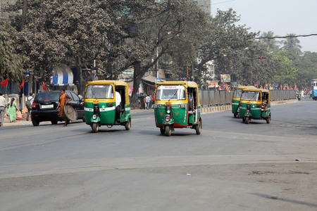 Private auto rickshaw three-weeler tuk-tuk taxi drives down the street on February 08, 2014 in Kolkata. Indian three-wheelers have the design of the Piaggio Ape C, from 1948