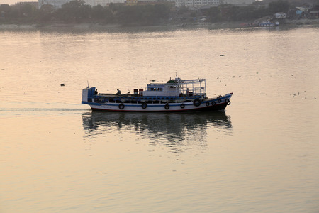 hooghly: Old ferry boat crosses the Hooghly River nearby the Howrah Bridge on February 08, 2014. To use the ferry is easy, fast and cheap way how to cross the Hooghly River.
