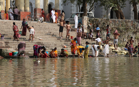 dome of hindu temple: Hindu people bathing in the ghat near the Dakshineswar Kali Temple on February 14, 2014. At present time this river is being polluted tremendously. Editorial