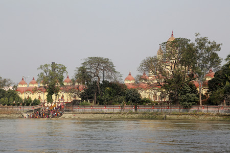 dome of hindu temple: Hindu people bathing in the ghat near the Dakshineswar Kali Temple on February 14, 2014. The beautiful temple was built in Bengal architecture style in 1855 Editorial