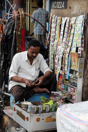 penury: Indian man outside a shop selling car parts on Malik bazar in Kolkata, India on February 08, 2014