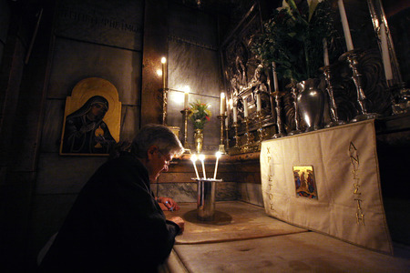 Pilgrims pray at the tomb of Jesus in the Church of the Holy Sepulchre, traditional site of the crucifixion, burial, and resurrection of Jesus, on October 01, 2006.
