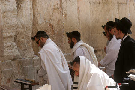 JERUSALEM - OCTOBER 03: Jewish men pray at the western wall October 03, 2006 in Jerusalem, IL. The wall is one of the holiest sites in Judaism attracting thousands of worshipers daily.