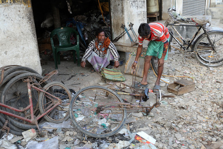 Mechanic in the workshop repair the bicycle. The bicycle is in India, one of the main means of transport, Kumrokhali, West Bengal, India