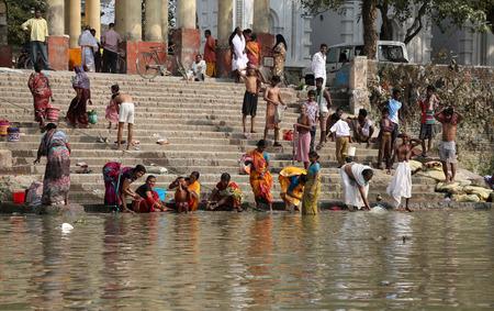 personas banandose: Los hind�es se ba�an en el ghat cerca del templo de Kali Dakshineswar el 14 de febrero de 2014. En la actualidad este r�o se est� contaminando enormemente. Editorial