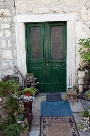 iron curtains: Mediterranean house with green door and flowers, on June 08, 2012 in Prcanj, Montenegro