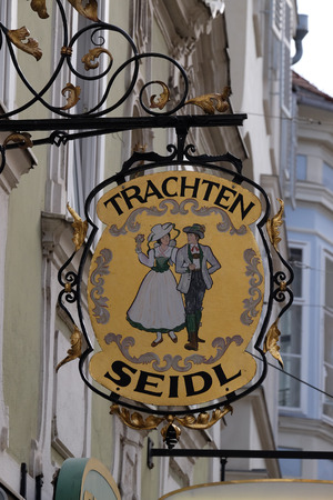 trachten: Old shop sign for Trachten Seidl made of wrought iron, hanging outside shop in the old town of Graz, Styria, Austria on January 10, 2015.