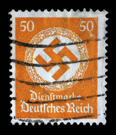 swastika: A postage stamp printed in Germany shows the Swastika in an oak wreath, circa 1942. Editorial