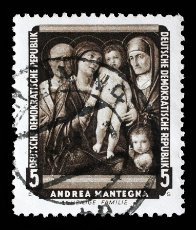 famous paintings: A stamp printed in DDR shows the painting Holy Family, by Andrea Mantegna , from the series Famous Paintings from Dresden Gallery, circa 1957.